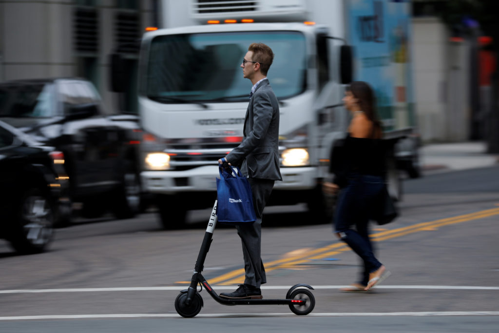 A man in a suit rides an electric BIRD rental scooter along a city street.REUTERS/Mike Blake - RC1EEA4B55E0